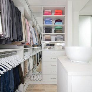 Immagine di un grande spazio per vestirsi unisex minimalista con ante lisce, ante bianche, parquet chiaro e pavimento beige