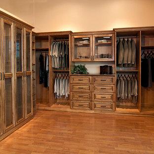 Foto de armario vestidor de hombre, clásico, grande, con armarios con paneles con relieve, puertas de armario de madera en tonos medios, suelo de madera oscura y suelo marrón