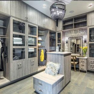 Diseño de vestidor de mujer, actual, grande, con armarios con paneles lisos, puertas de armario grises, suelo de madera clara y suelo gris