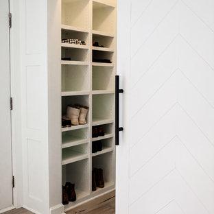Idéer för ett litet klassiskt klädskåp för könsneutrala, med mellanmörkt trägolv, öppna hyllor, vita skåp och brunt golv