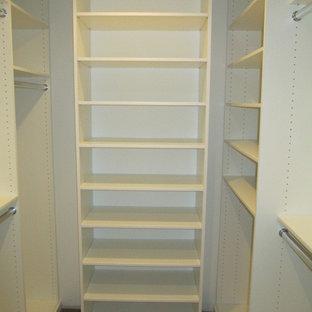 Idéer för att renovera ett litet funkis walk-in-closet för könsneutrala, med mellanmörkt trägolv, släta luckor, vita skåp och brunt golv