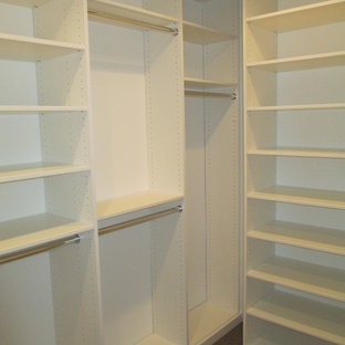 Small modern gender-neutral walk-in wardrobe in Los Angeles with medium hardwood floors, flat-panel cabinets, white cabinets and brown floor.
