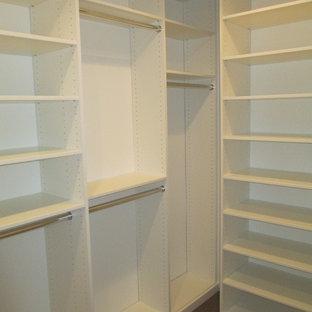Modelo de armario vestidor unisex, moderno, pequeño, con suelo de madera en tonos medios, armarios con paneles lisos, puertas de armario blancas y suelo marrón