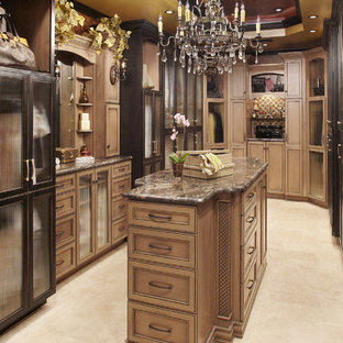 This is an example of a large classic dressing room for women in Dallas with recessed-panel cabinets, travertine flooring, beige floors and brown cabinets.