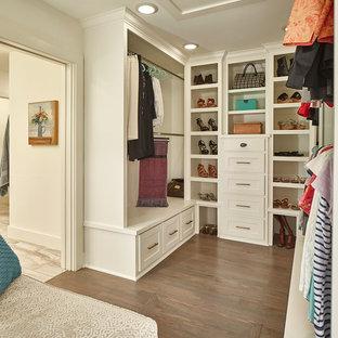 Idee per uno spazio per vestirsi unisex chic con ante in stile shaker, ante bianche, pavimento in legno massello medio e pavimento marrone
