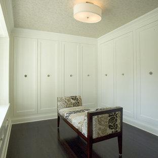 Ejemplo de vestidor unisex, bohemio, grande, con armarios estilo shaker, puertas de armario blancas y suelo de madera oscura