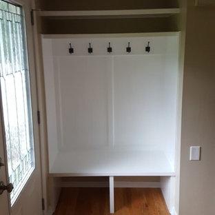 Idee per un piccolo spazio per vestirsi unisex chic con ante a filo, ante bianche e parquet chiaro