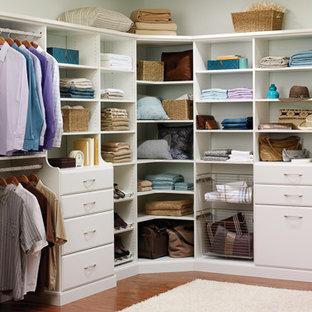 Imagen de armario vestidor unisex, clásico, de tamaño medio, con armarios con paneles lisos, puertas de armario blancas, suelo de madera oscura y suelo marrón