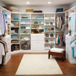 Foto de armario vestidor unisex, clásico, de tamaño medio, con armarios con paneles lisos, puertas de armario blancas, suelo de madera oscura y suelo marrón
