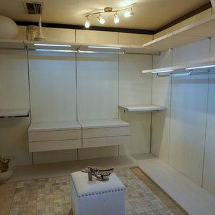 Ejemplo de armario vestidor de mujer, moderno, grande, con armarios abiertos, puertas de armario blancas y suelo de piedra caliza