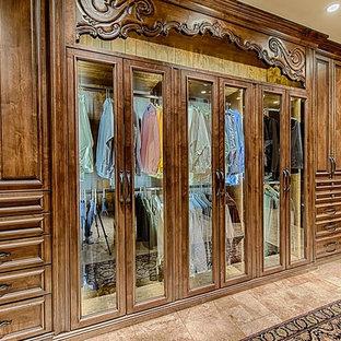 Diseño de armario vestidor de hombre, tradicional, grande, con armarios tipo vitrina, puertas de armario de madera oscura y suelo de mármol