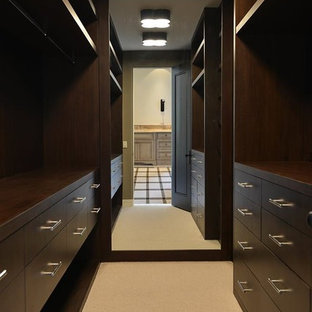 Inredning av ett modernt litet walk-in-closet, med släta luckor, skåp i mörkt trä och heltäckningsmatta