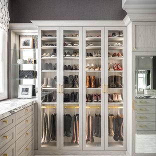 Immagine di uno spazio per vestirsi per donna chic con ante di vetro, moquette e pavimento grigio