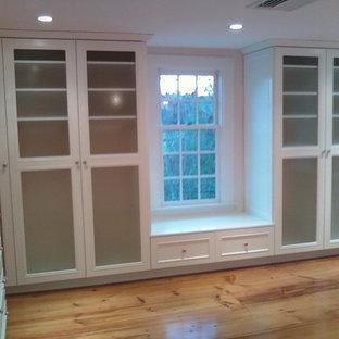 Ejemplo de armario vestidor unisex, moderno, grande, con suelo de madera clara