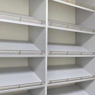 This is an example of a large contemporary gender-neutral walk-in wardrobe in Calgary with white cabinets.