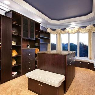 Ejemplo de armario vestidor actual, extra grande, con armarios con paneles lisos, puertas de armario de madera en tonos medios y moqueta