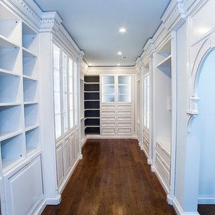 Modelo de armario vestidor de mujer, mediterráneo, grande, con puertas de armario blancas, suelo de madera en tonos medios y armarios tipo vitrina