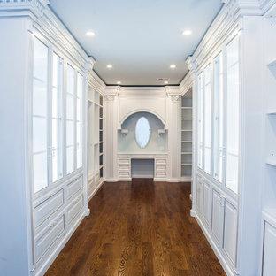 Idées déco pour un grand dressing méditerranéen pour une femme avec un placard à porte vitrée, des portes de placard blanches et un sol en bois brun.