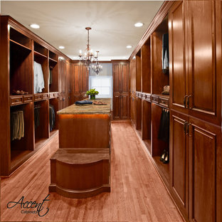 Inspiration for an expansive gender-neutral dressing room in Houston with raised-panel cabinets and medium wood cabinets.