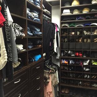 Imagen de armario vestidor unisex, tradicional, de tamaño medio, con armarios con paneles con relieve, puertas de armario de madera en tonos medios y moqueta