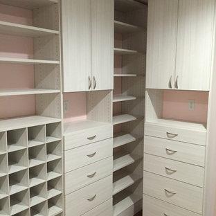 Ejemplo de armario vestidor de mujer, minimalista, de tamaño medio, con armarios con paneles lisos, suelo de madera en tonos medios y puertas de armario de madera clara