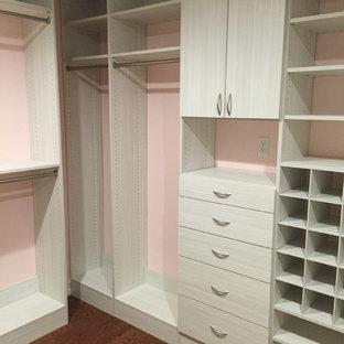 Ispirazione per una cabina armadio per donna moderna di medie dimensioni con ante lisce, ante in legno chiaro e pavimento in legno massello medio