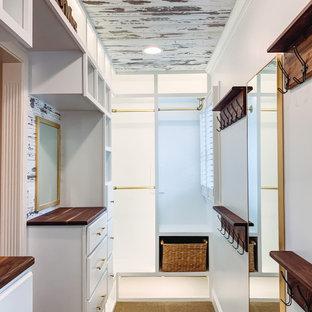 Idéer för en mellanstor lantlig garderob för könsneutrala, med luckor med upphöjd panel, vita skåp, heltäckningsmatta och beiget golv