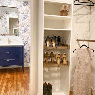 Ejemplo de armario vestidor pequeño con armarios con paneles lisos, puertas de armario blancas y suelo de madera en tonos medios