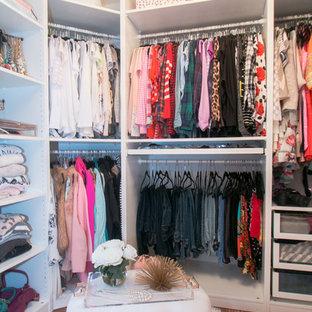 Foto de vestidor de mujer, actual, de tamaño medio, con armarios abiertos, puertas de armario blancas y suelo de madera en tonos medios