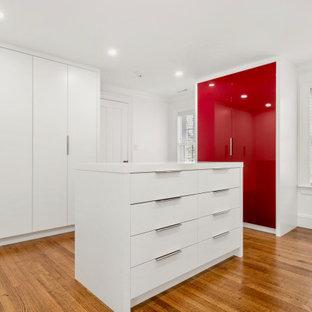 Imagen de armario vestidor unisex, contemporáneo, con puertas de armario rojas y suelo de madera en tonos medios
