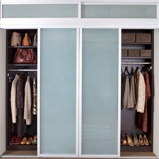 Exemple d'un grand placard dressing moderne neutre avec un placard à porte vitrée, moquette et des portes de placard en bois sombre.