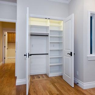 Modelo de armario unisex, tradicional, de tamaño medio, con armarios abiertos, puertas de armario blancas, suelo de madera en tonos medios y suelo marrón