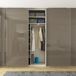 Ejemplo de armario unisex, minimalista, de tamaño medio, con armarios con paneles lisos, suelo de madera clara y puertas de armario grises