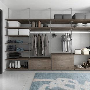 Ejemplo de armario vestidor unisex, minimalista, grande, con armarios con paneles lisos, puertas de armario de madera oscura, suelo de baldosas de cerámica y suelo gris