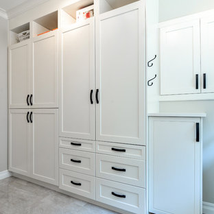 This is an example of a medium sized modern gender neutral wardrobe in Vancouver with recessed-panel cabinets, white cabinets and travertine flooring.