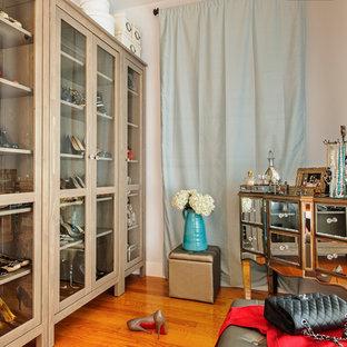 Diseño de armario vestidor de mujer, clásico, de tamaño medio, con armarios tipo vitrina, puertas de armario de madera clara, suelo de madera en tonos medios y suelo marrón