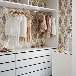 Imagen de armario vestidor de mujer, romántico, de tamaño medio, con armarios abiertos, puertas de armario blancas, suelo de madera oscura y suelo marrón
