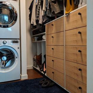 Foto di una piccola cabina armadio unisex minimalista con ante lisce, ante in legno chiaro, pavimento in cemento e pavimento marrone