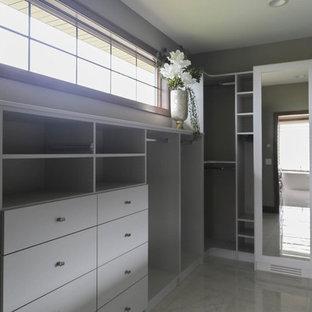 Imagen de armario vestidor unisex, clásico, de tamaño medio, con armarios con paneles lisos, puertas de armario blancas, suelo de baldosas de porcelana y suelo blanco