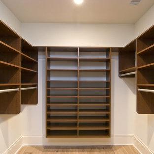 Inspiration for a mid-sized transitional gender-neutral light wood floor and beige floor walk-in closet remodel in Boston with open cabinets and dark wood cabinets