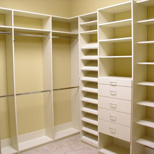 Inredning av ett klassiskt mellanstort walk-in-closet för könsneutrala, med öppna hyllor, vita skåp, heltäckningsmatta och beiget golv