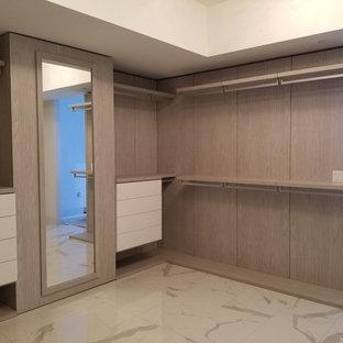 Modern inredning av ett stort walk-in-closet för könsneutrala, med släta luckor, skåp i mörkt trä, marmorgolv och flerfärgat golv