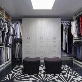 Immagine di una cabina armadio unisex moderna di medie dimensioni con ante lisce, ante grigie, pavimento in gres porcellanato e pavimento nero