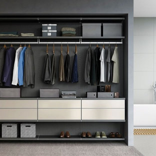 This is an example of a mid-sized modern men's built-in wardrobe in San Diego with flat-panel cabinets and carpet.
