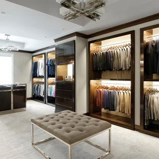 Imagen de vestidor de hombre, contemporáneo, con armarios abiertos, puertas de armario de madera en tonos medios, moqueta y suelo beige