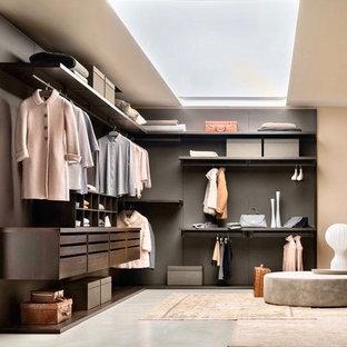 Inredning av ett modernt stort walk-in-closet för könsneutrala, med öppna hyllor, bruna skåp, betonggolv och grått golv