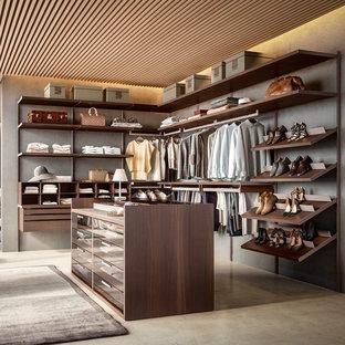 Modelo de armario vestidor unisex, contemporáneo, grande, con armarios abiertos, puertas de armario marrones, suelo de cemento y suelo beige