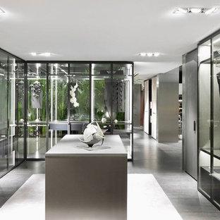 Idées déco pour un grand dressing contemporain neutre avec un placard à porte plane, des portes de placard marrons, un sol en bois brun et un sol gris.