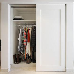 Immagine di un piccolo armadio o armadio a muro unisex minimal con ante lisce, ante bianche, pavimento in gres porcellanato e pavimento beige