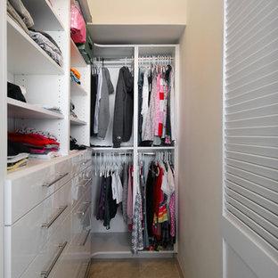 Ejemplo de armario vestidor unisex, contemporáneo, pequeño, con armarios con paneles lisos, puertas de armario blancas, suelo de baldosas de porcelana y suelo beige